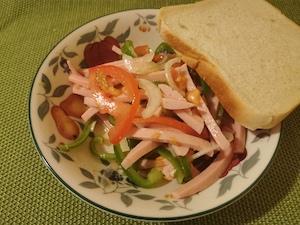 Wurstsalat mit einer Scheibe Toastbrot.